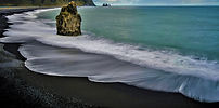 Waves crash on the scenic black sand beaches of Vík in Iceland