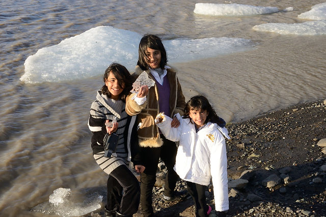Three girls hold pieces of glacier on their fun family adventure trip to Iceland
