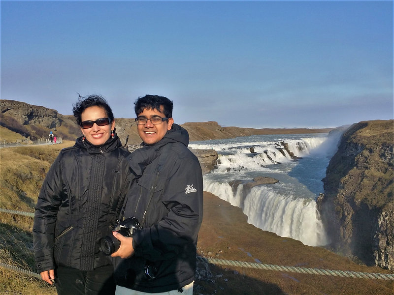 A woman and a man stand in front of the Gullfoss waterfall in Iceland, which is a short drive from Reykjavik
