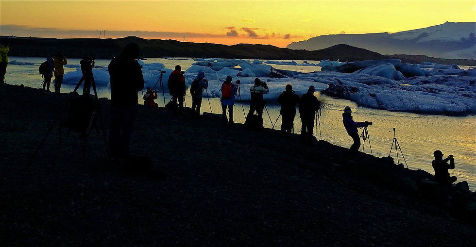 A crowd of photographers shoot the scenic Jökulsárlón glacier in Iceland during twilight