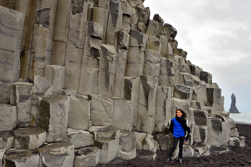A girl stands on the windy black sand beaches of Vík in Iceland in a landscape filled with hexagonal stone structures