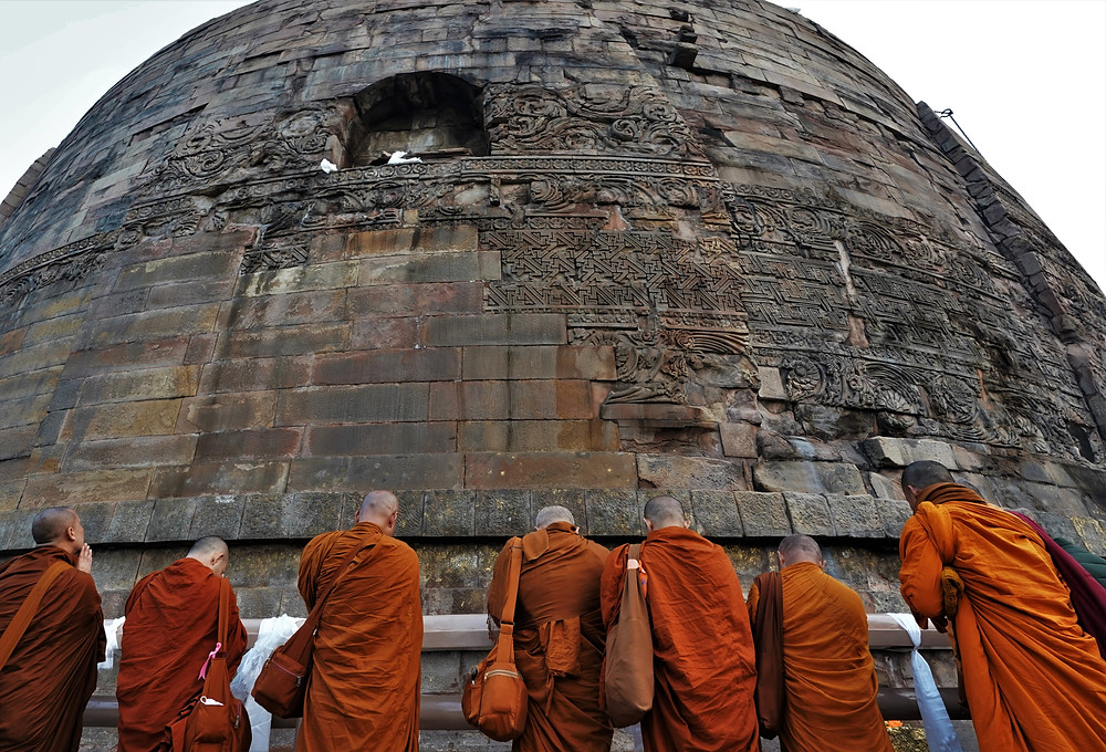"""With the approach of sunset, monks pray around the """"stupa"""" at Sarnath, near Varanasi. This is where Gautama Buddha gave his first sermons and is widely regarded as one of the holiest of the Buddhist sites."""