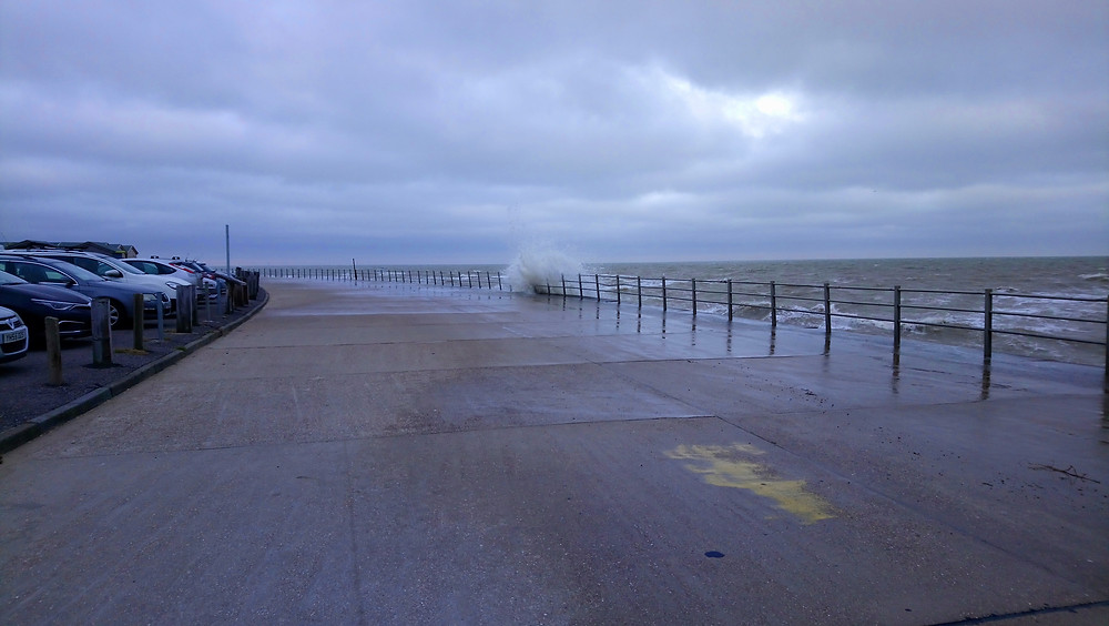 One of the waves crashing over the sea wall