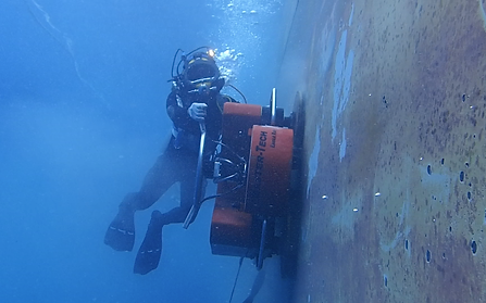 A commercial diver using a brush cart to clean the vertical plating of a vessel. Image provided by Master Tech Diving Services Pte Ltd.