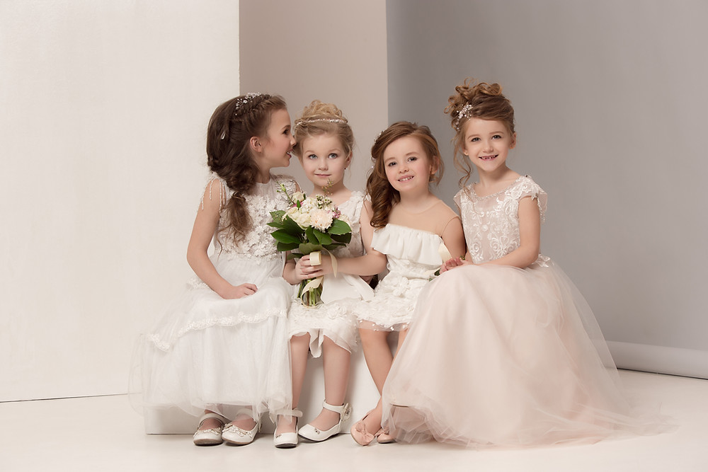 Four little girls sit next to each other. They're all dressed like brides and one is holding a bouquet of flowers.