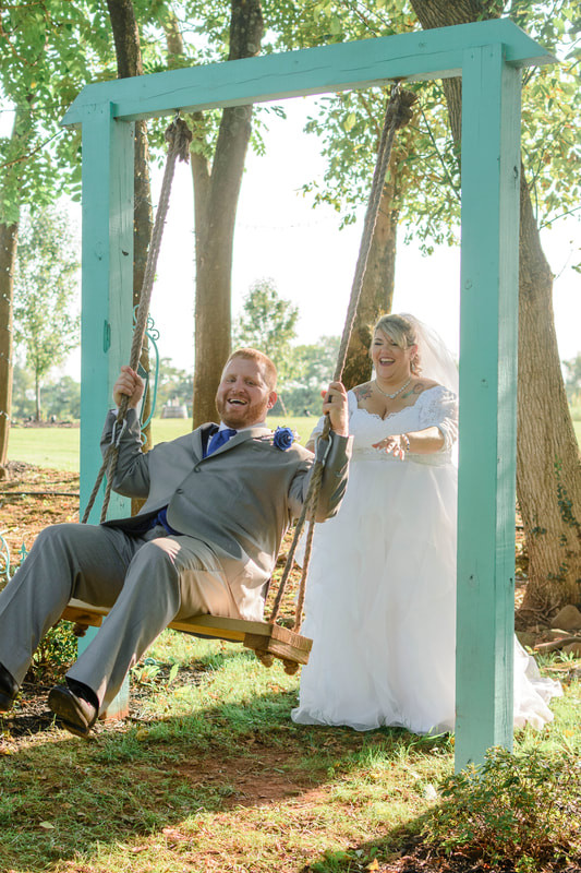 A bride pushing a groom on a large garden swing.
