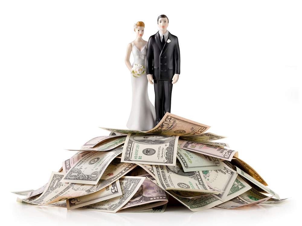 A cake topper of a bride and groom on top of a pile of money.