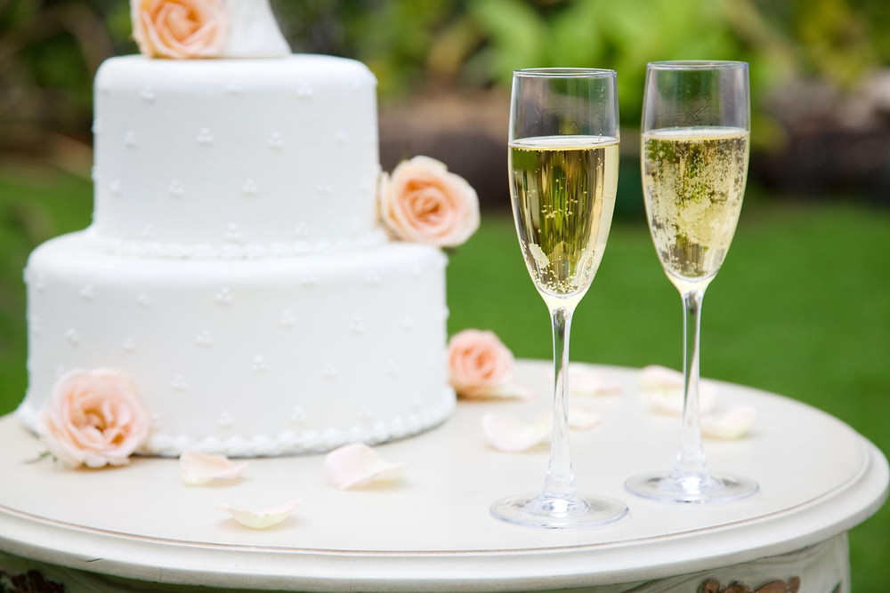 Two champagne glasses sit on a table next to a white wedding cake with pink roses.