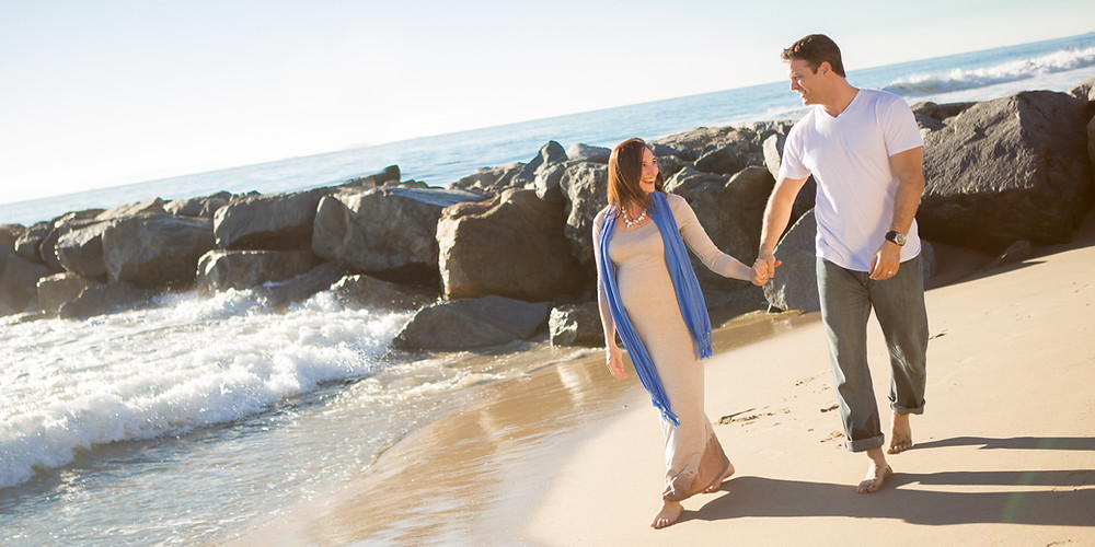 Pregnant woman walking in the beach with his husband, man, baby, expecting, dress, blue scarf.