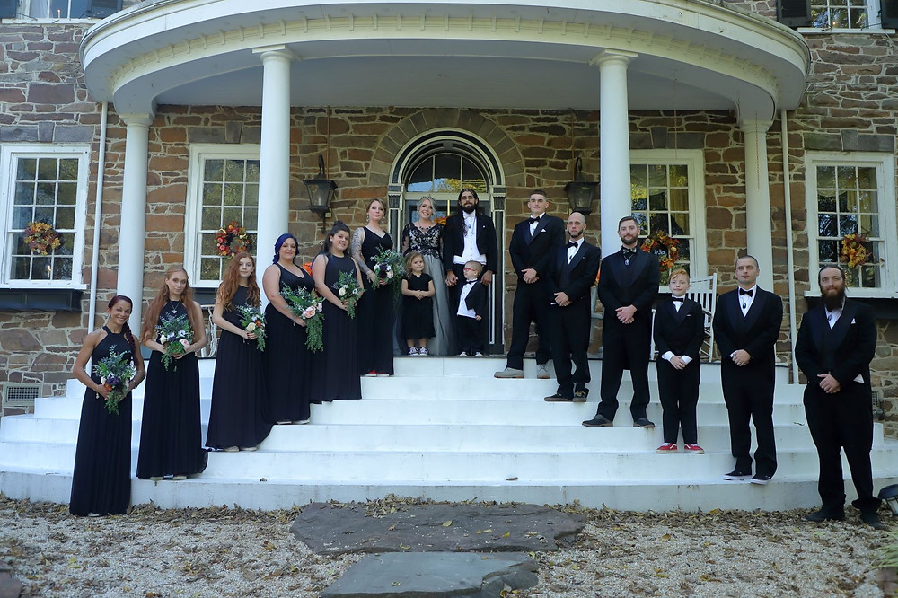 A bridal party standing on the front steps of a house.