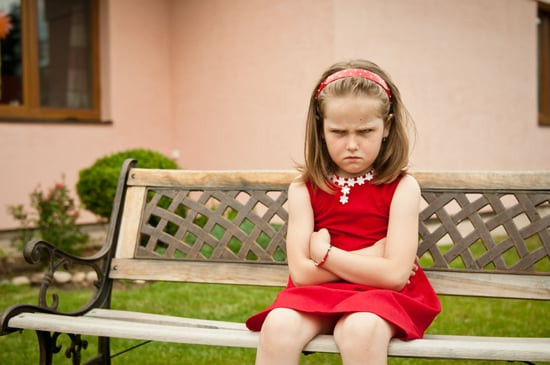 A little girl sits on a bench with her arms crossed and an angry look on her face.