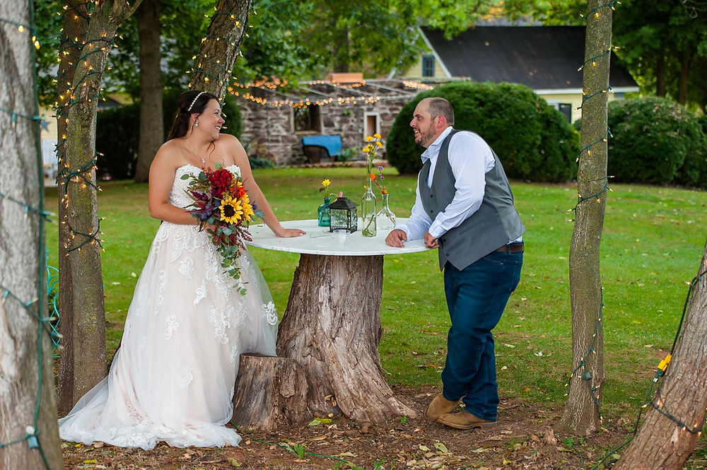 A bride and groom look lovingly at each other across a cocktail table made from a tree stump.