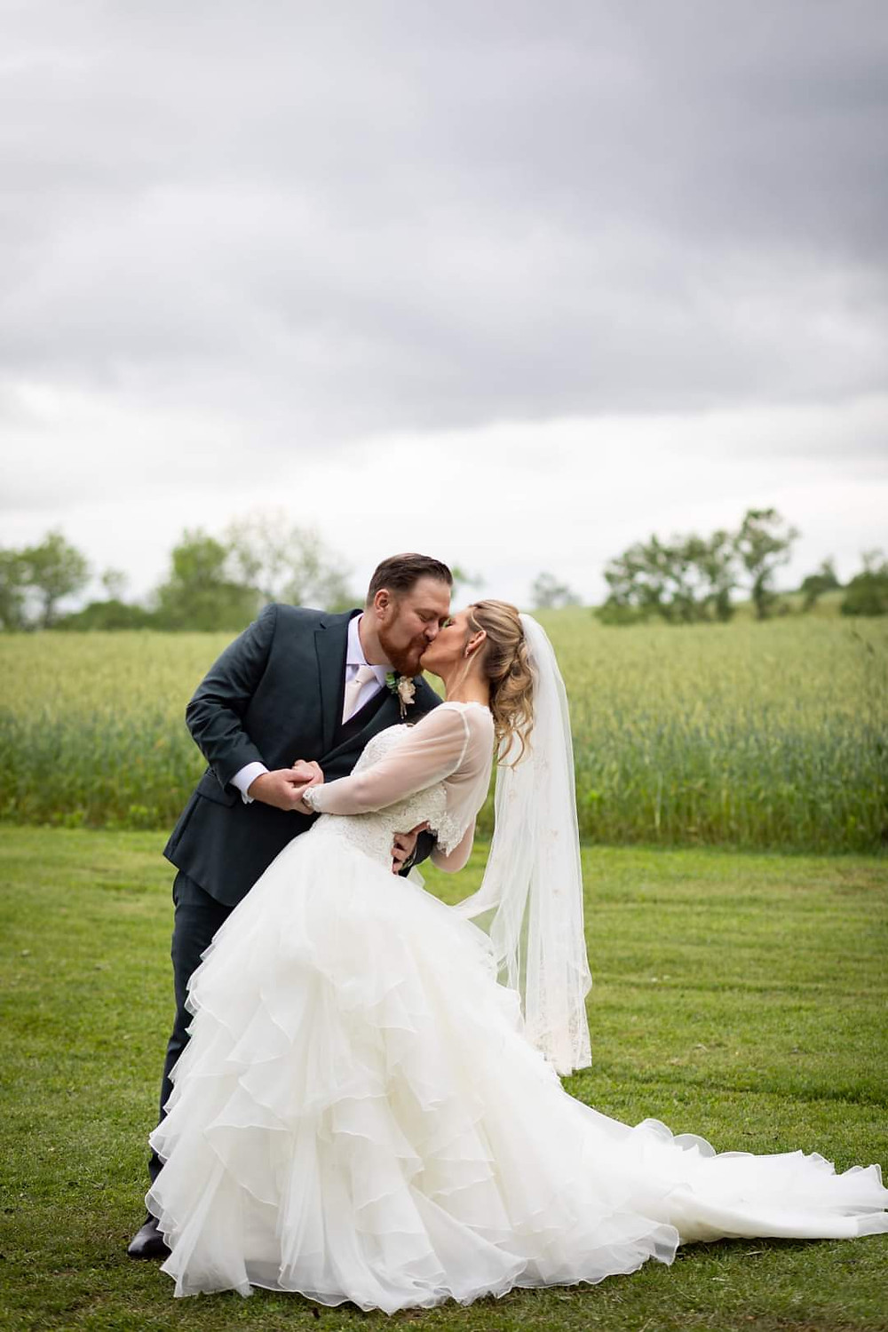 A bride and groom are kissing in front of a field of wheat.
