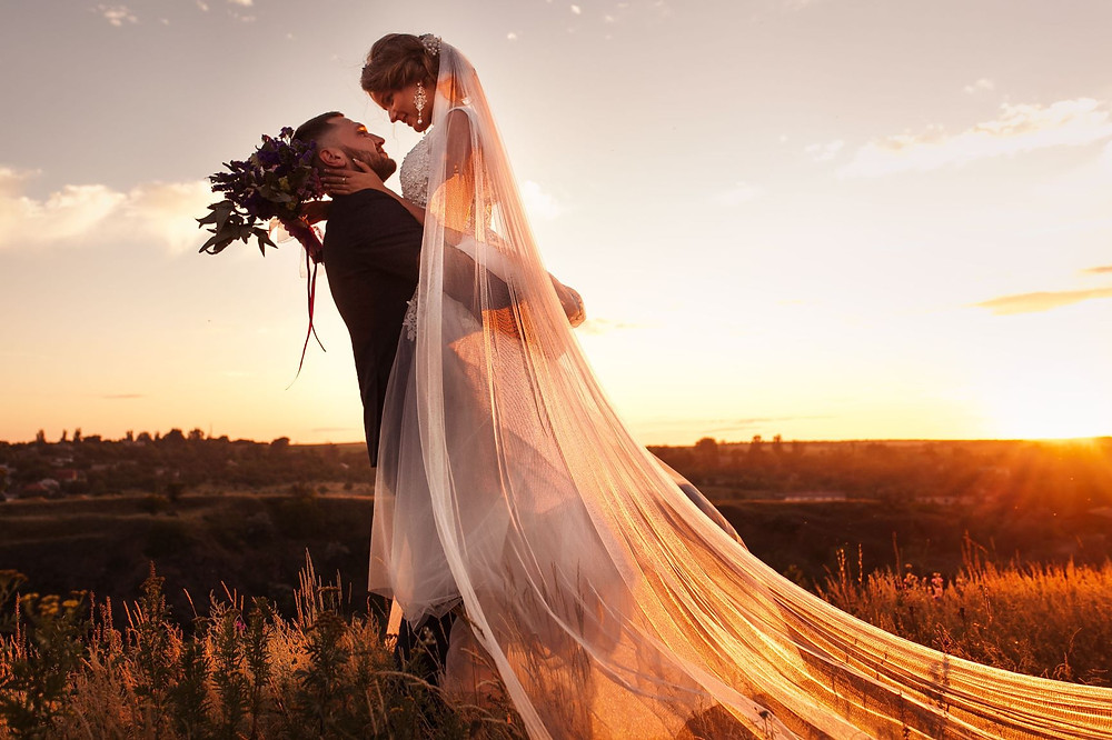 A bride and groom are standing in a field at sunset. The groom is holding the bride up in the air.