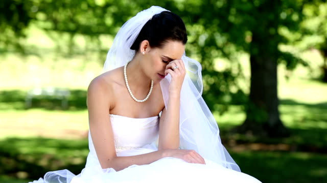 A bride sitting outside. She is clearly upset.