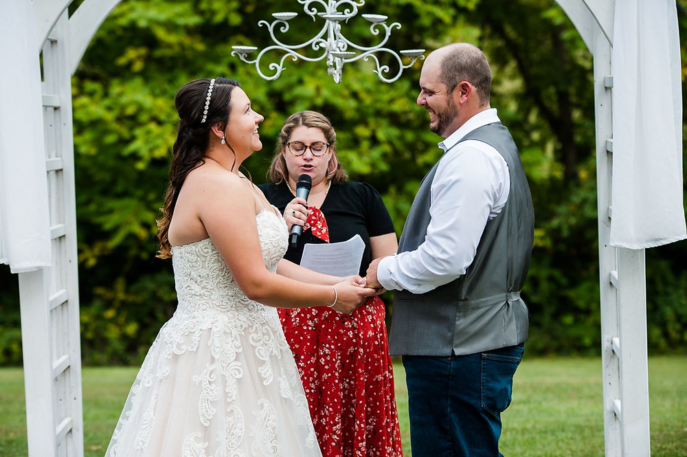 A loving couple stands at the wedding arbor during their ceremony. They are standing hand in hand.