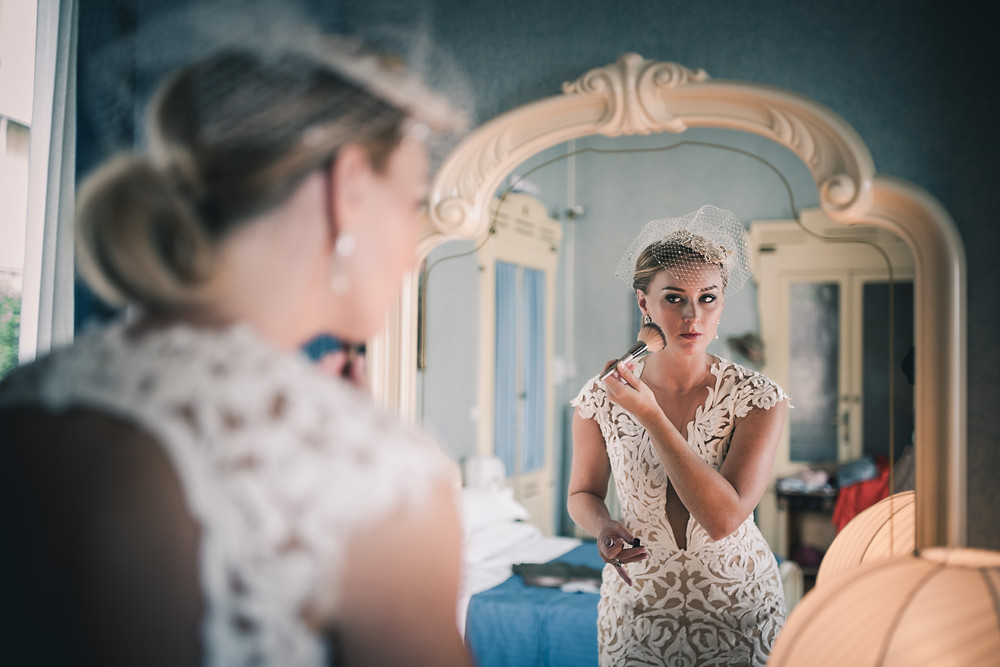 bride getting ready in key whole back wedding dress
