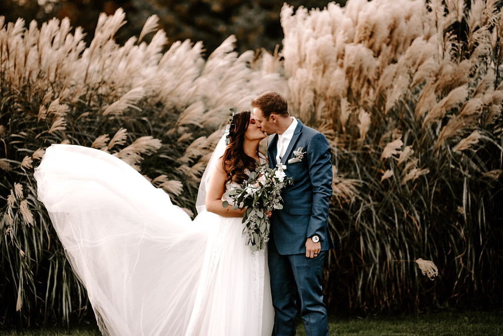 lace wedding dress and navy suit groom