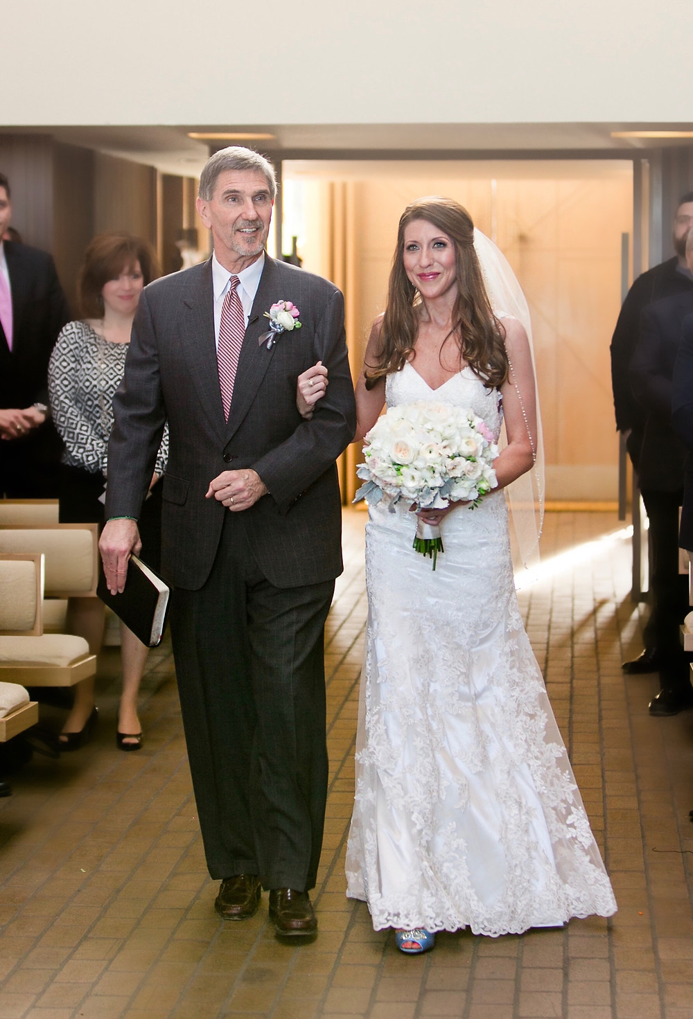 bride walking down the isle with father with white rose bouquet