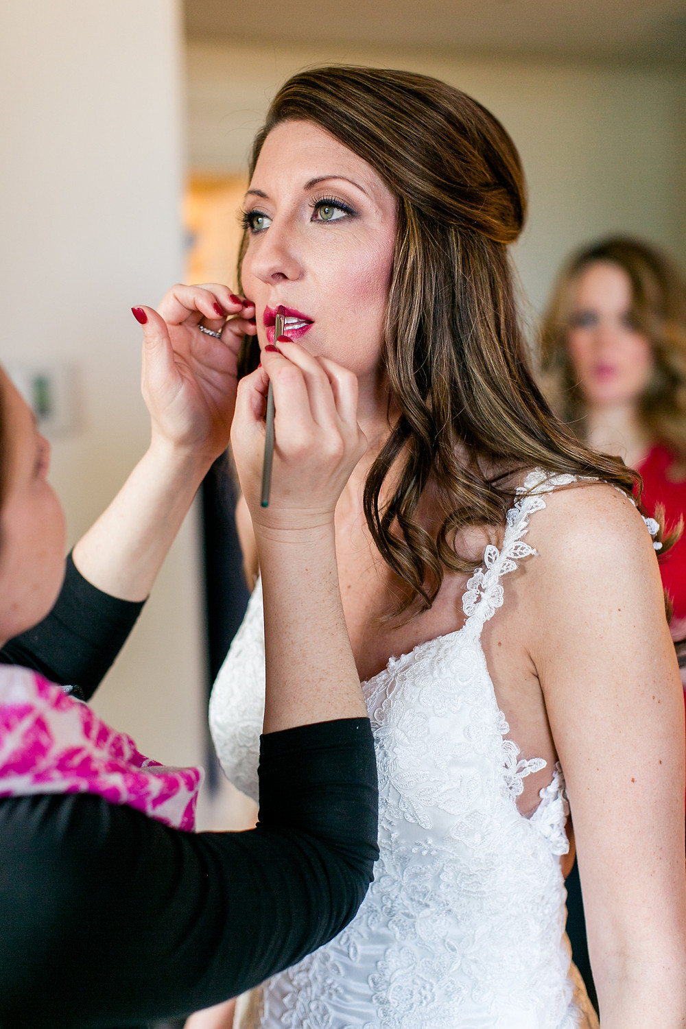 bride getting ready in spaghetti strap lace gown