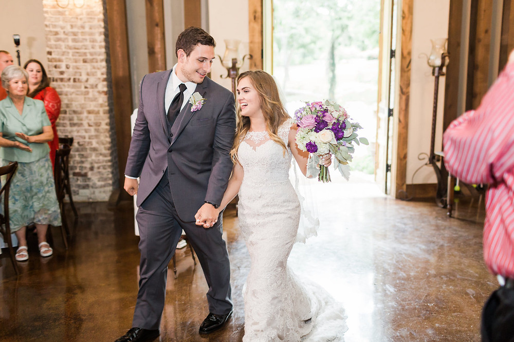 bride and groom with purple floral bouquet