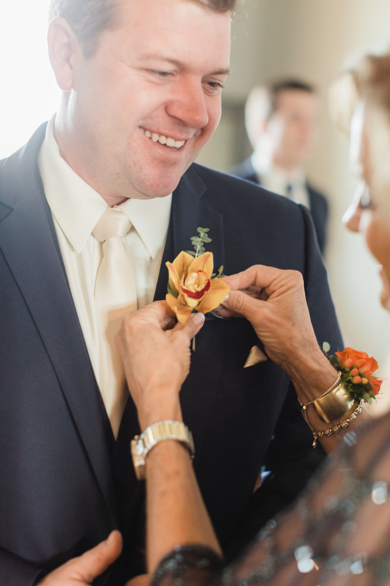 groom and orange boutonniere