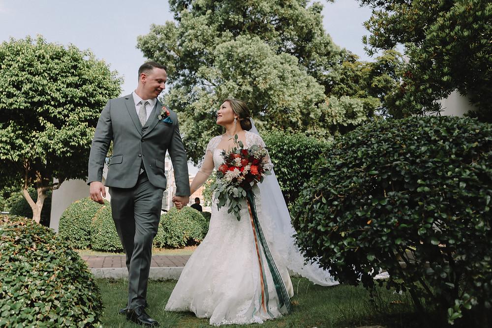 bride and groom walking through the garden