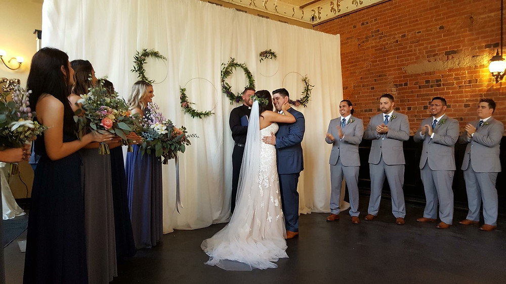 bridal party and groomsmen with happy couple