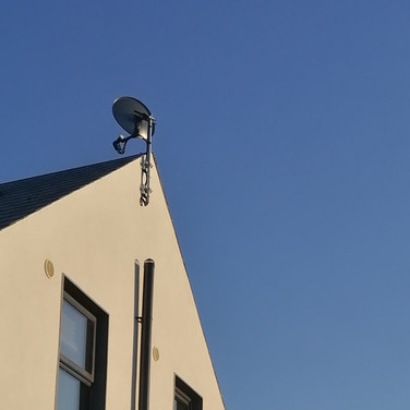 Satellite dish mounted on the pole that allows satellite signal to pass trees  in Naas Co Kildare