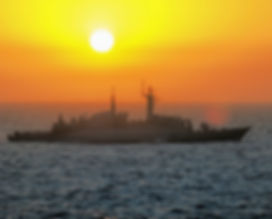 Naval navy ship in open sea during sunset