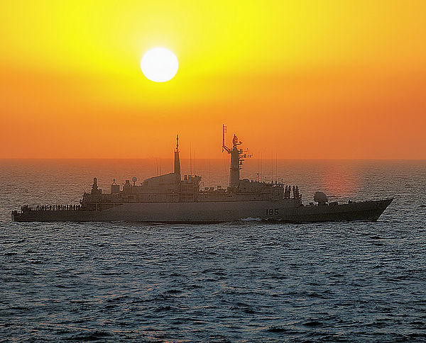 Naval navy ship in open sea during sunse