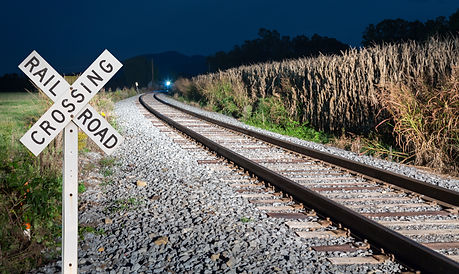 Oncoming train with railroad crossing si