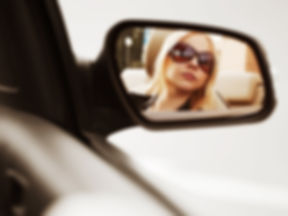 Young woman looking in the car mirror_ed