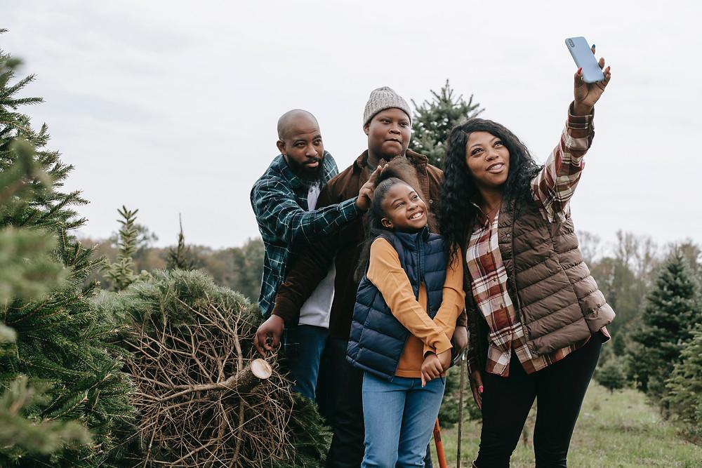 Family taking photo at Christmas tree farm