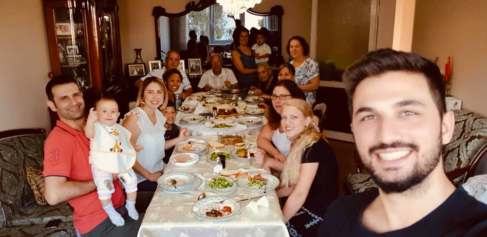 Dina's family at a large table for a family gathering in Turkey.