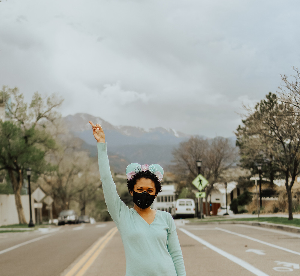 Travel Advisor Dina Farmer Standing on a street in Colorado Springs in front of Pikes Peak with Mouse Ears on and holding up a peace sign.