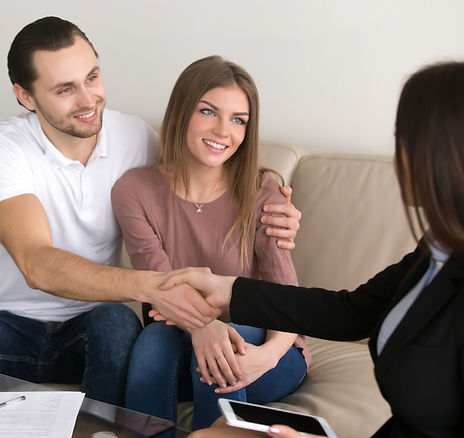 New homeowner couple shaking hands with loan officer.