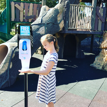 Sunstation sunscreen dispenser being used by child