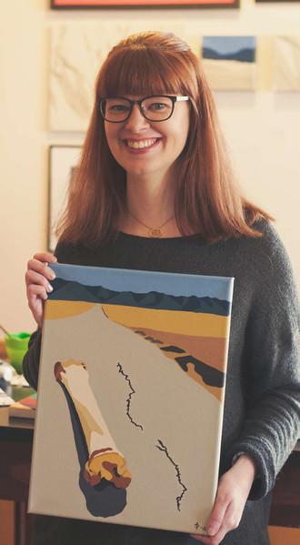 Artist Amanda Porter holding her painting Dry Bone in the Wasteland.