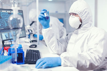 lab-technician-dressed-in-protective-suit-as-safety-precaution-looking-at-test-tube.jpg