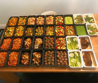 A table full of containers of food ready for the freezer and refrigerator