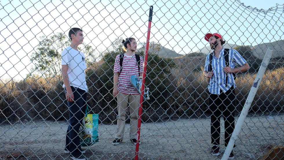 Drei Skater warten vor einem Zaun in Kalifornien, USA