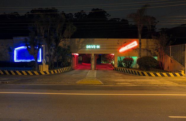 Ein Drive In in Sao Paulo, Brasilien. Viele Neon Lichter per Nacht. In der Mitte sieht man die Neon Schrift 'Drive In'