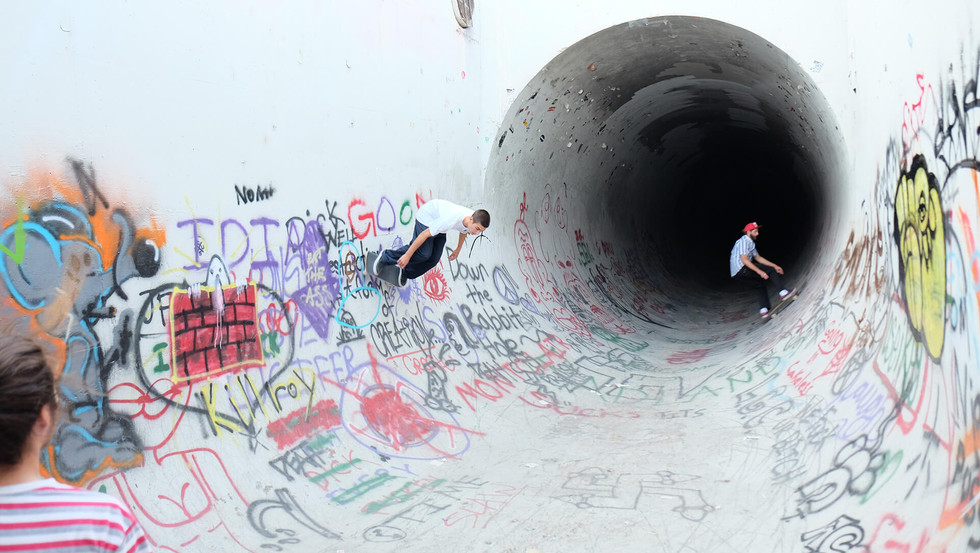 Zwei Skater skaten in dem Abwasser Rohr in Kalifornien, USA