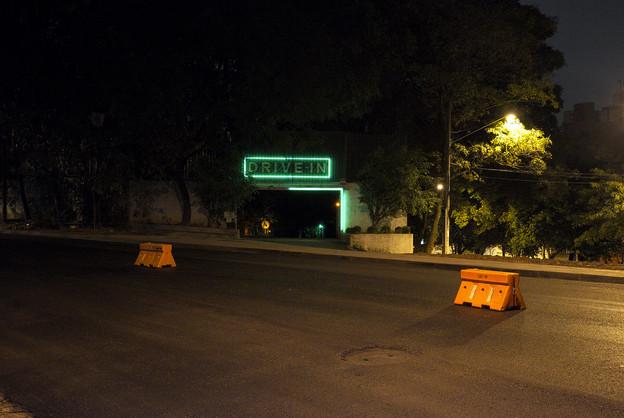 Der Eingang eines Drive In's in Sao Paulo, Brasilien. In der Mitte ein Schild 'Drive In' mit grünem Neon Licht.