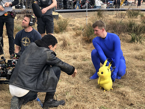 A puppet of Detective Pikachu is being filmed in grass, operated by puppeteer Mikey Brett and performing opposite actor Justice Smith
