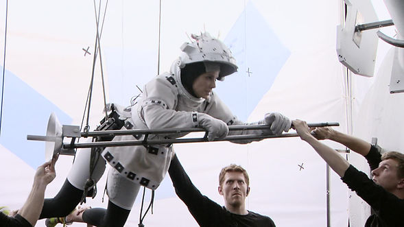 Sandra Bullock on the set of the film Gravity is being flown on a harness while puppeteers Mikey Brett and Robin Guiver work around her.