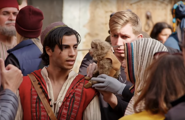 Mena Massoud, as Aladdin, is speaking to Abu the monkey - a puppet performed by Mikey Brett - with Naomi Scott as Princess Jasmine