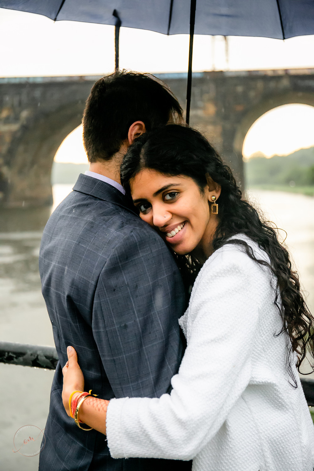 Girlfriend is hugging and smiling boyfriend under the umbrella during engagement session with South NJ Photographer Anett Mindermann Photography