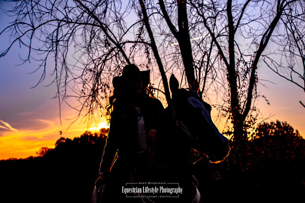 Cowgirl riding her horse at sunset